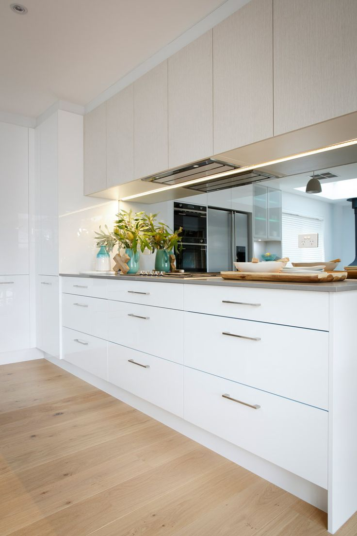 Washed grain look above head cabinetry with white cabinetry below dark coloured bench top