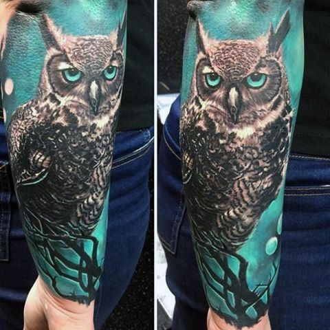 Awesome multicolored big mystic owl tattoo on sleeve