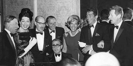 Irving Berlin, at the piano, is flanked by entertainers George Jessel, Rosalind Russell, Groucho Marx, Frank Sintra, Dinah Shore, Dean Martin, Danny Kaye