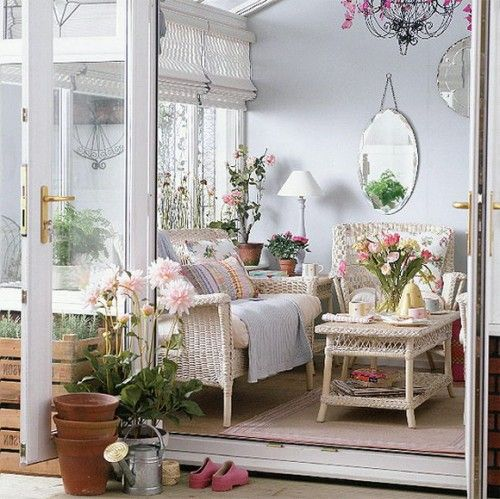 Surrounded by flowers and open airy windows this sun room has an awesome setting. The wicker sofa set and french provencal detailing are so appealing. It is so welcoming and absolutely charming! I want one.:
