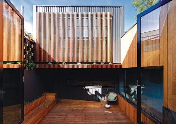 "On the far side of the courtyard, the ""tree house"" main suite, with its timber battens over glass, overhangs the sunken studio.  Parure House by Architects EAT"