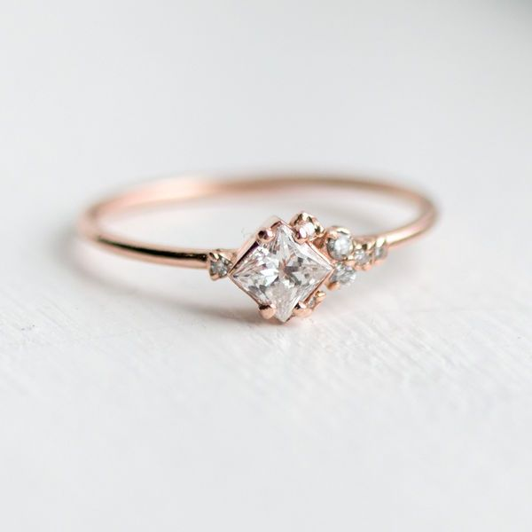 Princess Cut Diamond Cluster Engagement Ring: While many cluster engagement rings can be quite elaborate, there's also a place for a dainty bauble in this trend. This find is just as gorgeous as the rest with its petite charm. | 11 Heart Fluttering Cluster Engagement Rings
