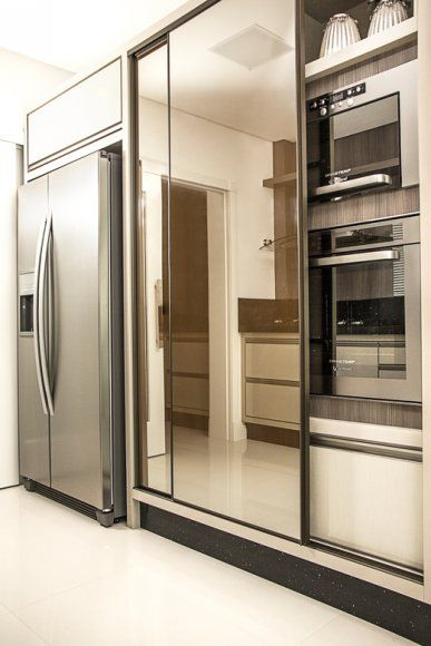Na cozinha, a designer optou por lâminas ciliegio em laca brilho e fendi confort fosca para contrastar, no acabamento do mobiliário.