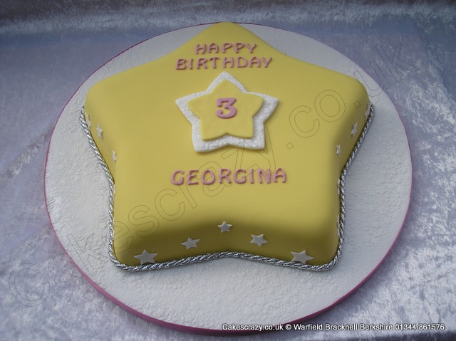 Star Cake. Star shaped birthday cake covered in yellow icing with a multi layered centre star on ...