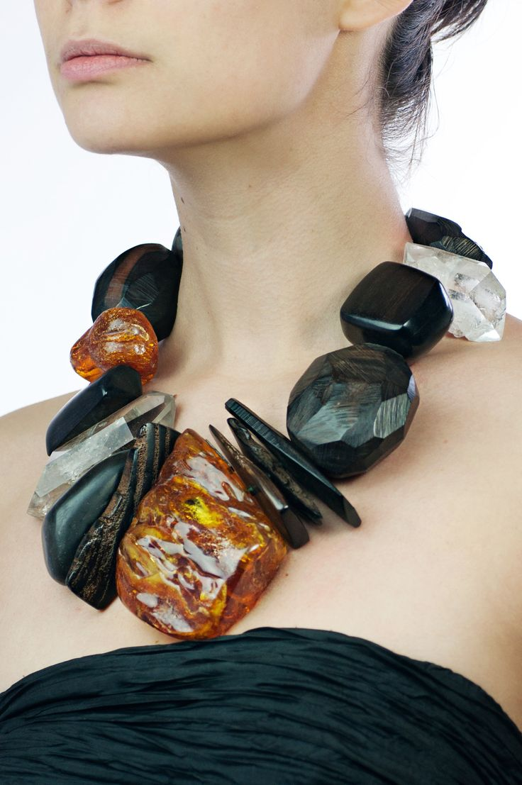 "Monies Amber, Ebony, and Crystal Necklace Monies Amber, Ebony, and Crystal Necklace. Large amber and ebony chunks enhance the crystals. Strung on leather. Material: Amber, Ebony, Crystal Color: Black, Orange, Clear Length: 18.5"" at neckline  $4825"