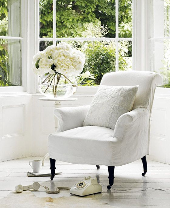Slip Covered Comfy Reading Chair, Lots Of Windows Out To Greenery, Clear  Glass Vase Of White Flowers, White Painted Wood Plank Floor.