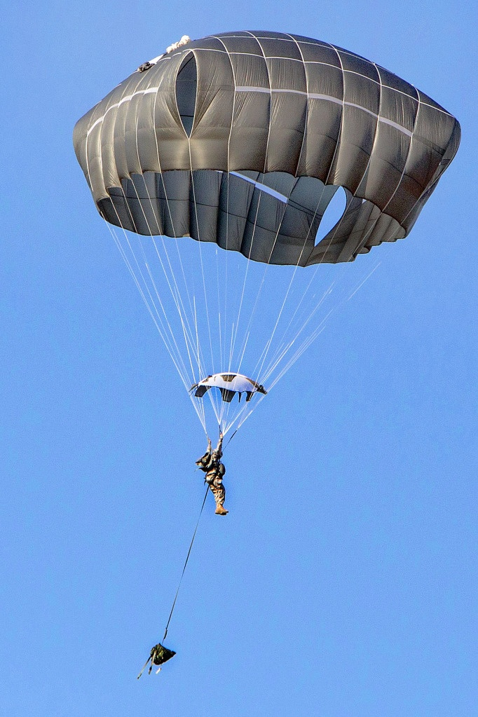 A paratrooper with the 82nd Airborne Division's 1st Brigade Combat Team descends to a drop zone on Fort Bragg, N.C., Jan. 29, 2013. Suspended below him is a rucksack, which will hit the ground first.