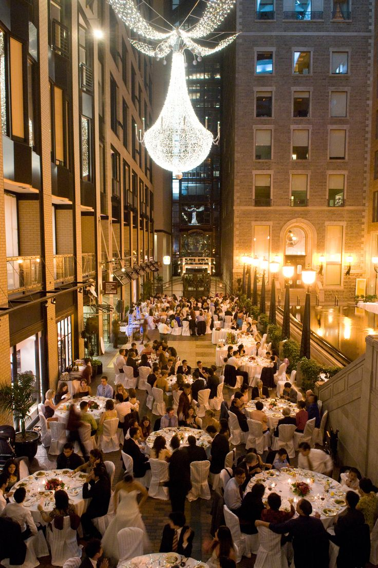 Wedding reception at the Intercontinental Hotel in Montreal in the Ruelle. This location is originally between two buildings that has been closed by the atrium on top. So you get a lovely feeling of being outside in a courtyard with lampposts without actually needing to worry about rain. Together with a glass fountain and dramatic suspended chandelier, this makes for a magical location for your wedding. Event by: MJ Weddings & Events (mjweddings.com)