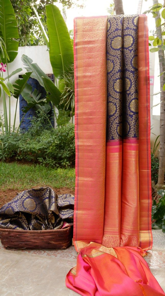 This rich kanchivaram silk is in midnight blue with a traditional, heavy pattern in gold zari. The border is in pink with intricately woven gold zari and a hint of violet and magenta while the pall…