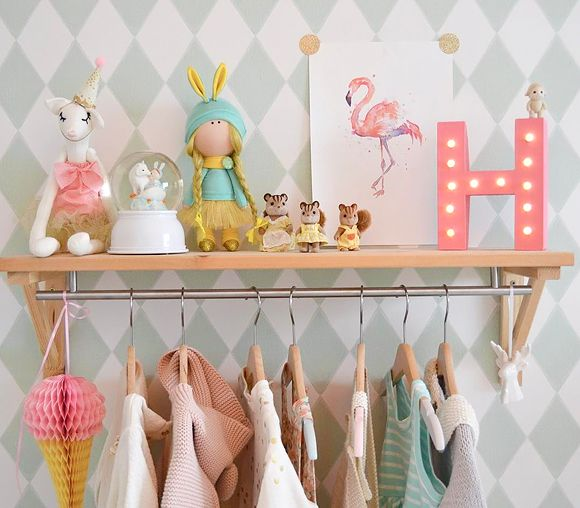 Une penderie bébé ou enfant en bois clair avec des vêtements mode