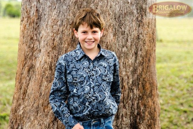 Boys Western Shirt | Blue Paisley Shirt | Brigalow Country Clothing. Our boys shirts are built tough - to survive boys. This 100% cotton, silvery blue coloured paisley print boys shirt is one of two in a series, and is also available in matching Mens sizes. The blue/silver/black paisley combination pattern not only looks great for dressy occasions, but also helps mask any scuff or dirt marks that country boys have a talent for accruing just before photo time.