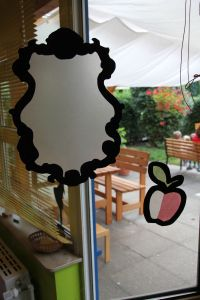Fensterbild: Spiegel und Apfel zum Märchen Schneewittchen und die sieben Zwerge.