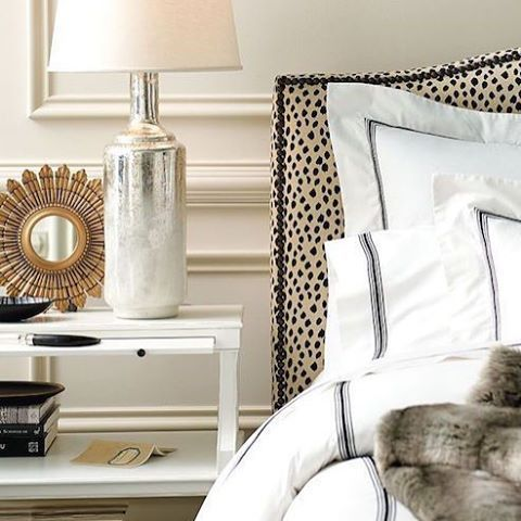 Neutral bedroom decor with some glam from the gold accents and leopard upholstered headboard