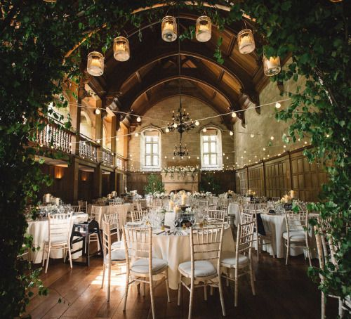 The vaulted roof is a stunning backdrop for this wedding setting, decorated with lights and foliage.