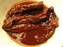 Wiki: Adobo or Adobar (Spanish: Marinade, Sauce, or Seasoning): Immersion of raw food in a stock (or sauce) composed variously of paprika, oregano, salt, garlic, & vinegar to preserve & enhance its flavor. Portuguese: Carne de vinha d'alhos. Native to Iberia (Spain, Portugal). It was widely adopted in Latin America & other Spanish & Portuguese colonies, incl. the Azores & Madeira. Philippines:  Spanish colonists named an indigenous cooking method that also uses vinegar, adobo - Wikipedia