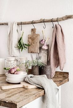 Rustic White Kitchen with Wood Plank Countertop, Branch with Hooks Hanging Storage, Glass Jars, Distressed Metal Pots