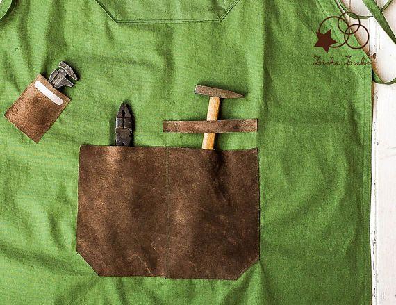 Grembiule uomo - grembiule artigiano - grembiule falegname - grembiule cuoco - grembiule pelle - grembiule tela  Il grembiule da lavoro è realizzato in tela cerata di lino 100% di colore verde militare, un tessuto resistente dalla mano asciutta ma comodo da indossare.  I lacci del grembiule sono lunghi e regolabili.  Sono presenti due tasche centrali. La tasca piccola in alto ha uno scomparto per penne o matite mentre la tasca grande in basso è suddivisa in due scomparti, quello di sinistra…