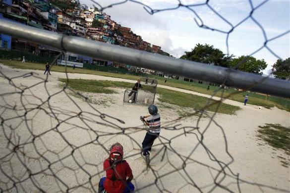 """Children practice during a baseball game at the """"Mamera"""" neighborhood in Caracas March 10, 2011.  REUTERS/Jorge Silva"""