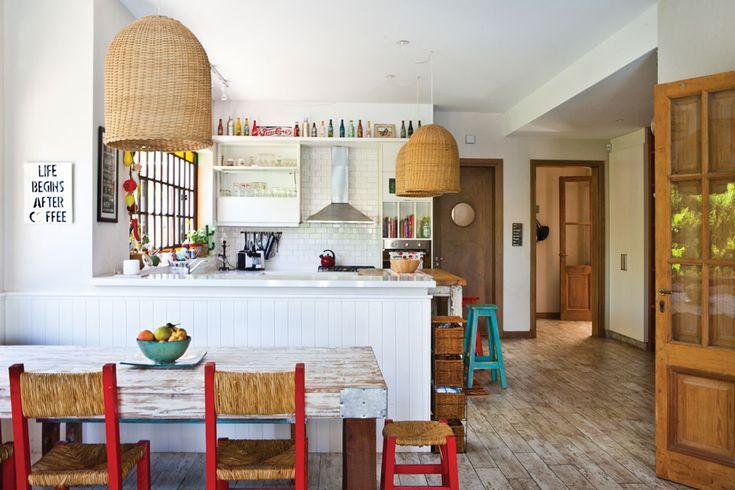 Una cocina elegante sport  En el comedor diario, se colocó una mesa de pino Oregón con enchapado en las esquinas y decapado blanco contra un paño fijo que enmarca una vista linda y luminosa.