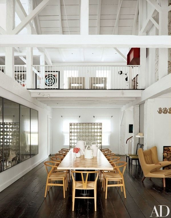 The double-height formal dining area, occupying part of the original barn, is furnished with chairs designed by Hans J. Wegner for Carl Hansen & Son and a custom-made table by India Mahdavi | archdigest.com