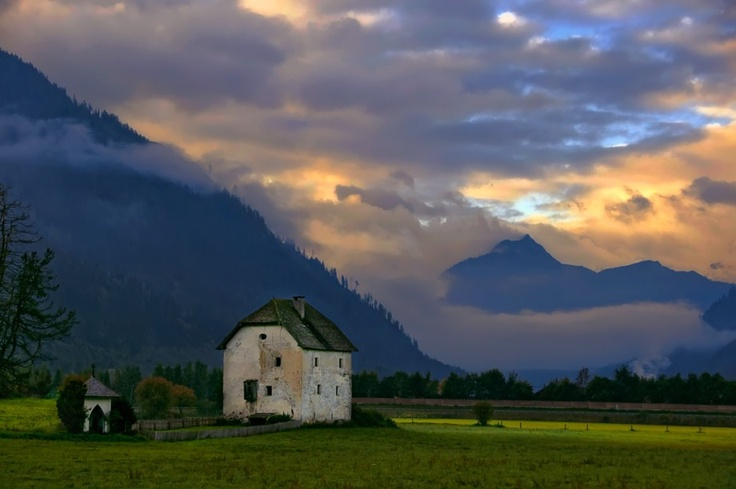 Lonely rustic cottage is in the middle a huge field in the Flachau (Salzburg, Austria) .  Tags: mountains, field, village, house, Austria