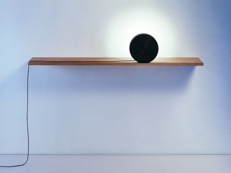 The Eclipse light with shelf is an ode to the union of opposites. The black aluminium reel and the white light reflected on the surface of the wall behind form a dynamic, symbiotic contrast. The rolling light source can be horizontally adjusted to fit to the composition of objects wanted to be displayed on the shelf. The cord neatly spins around the black reel while rolled to the wanted position. Design: Elina Ulvio