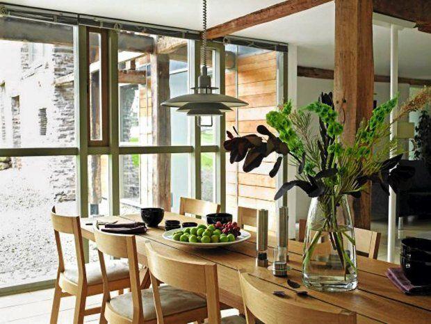 W jadalni przewidziano miejsce dla co najmniej 8 osób. Ciepła kolorystyka drewnianych mebli kontrastuje z połyskującymi srebrem ramami okiennymi i lampą