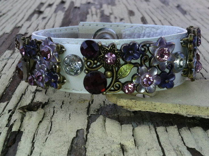 one of a kind hand made leather cuff adorned with rhinestones and flowers.