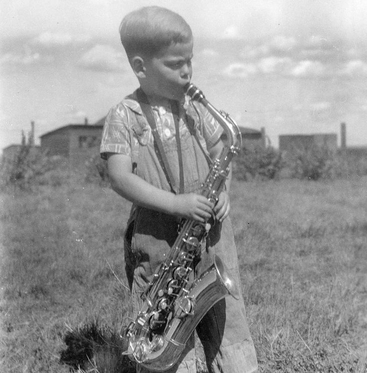 Young Phil Plays his Sax.....Phil Washburn playing saxophone, on farm in Vulcan area, Alberta.... [ca. 1945-1946], Phil Washburn was born in 1941.