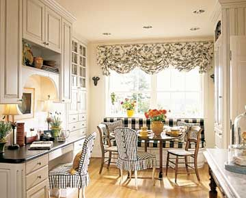 Striking black-and-white fabrics, antique chairs, and an antique wine-tasting table combine to give this banquette French-country charm.