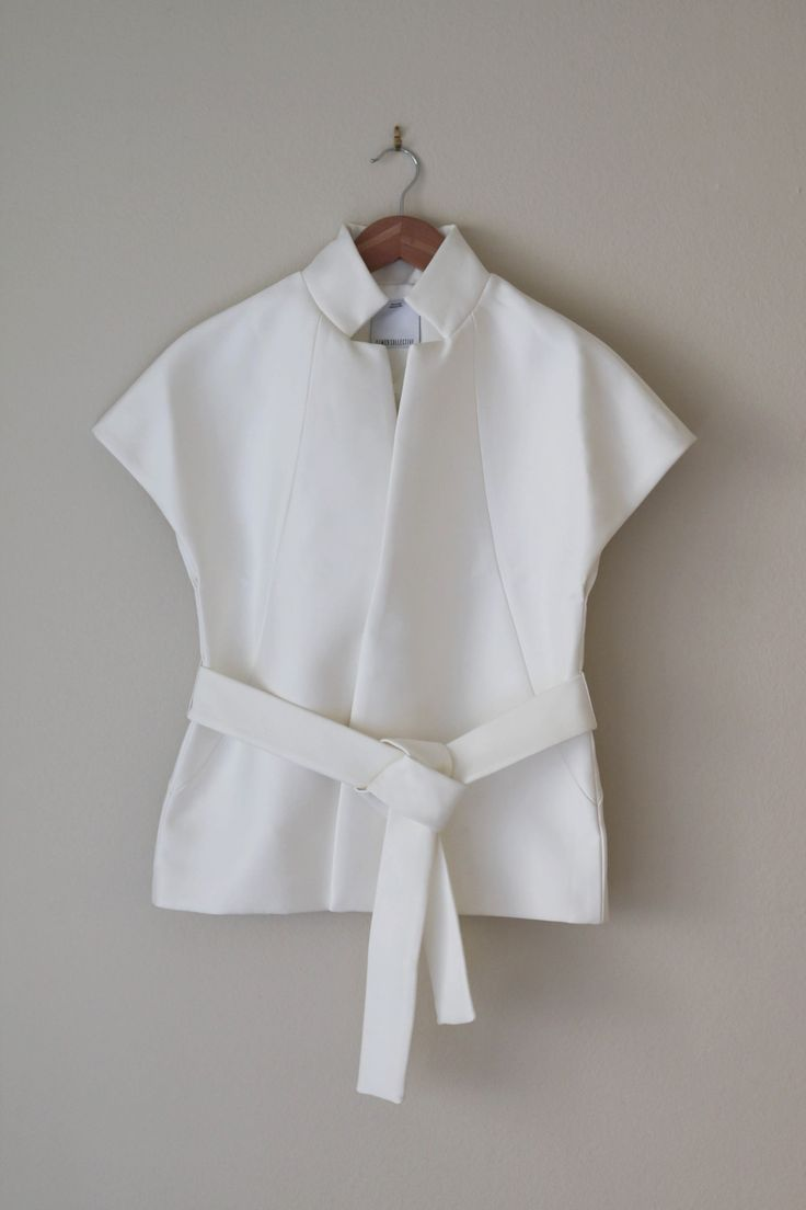 From C/MEO COLLECTIVE, a mid weight boxy top with structured silhouette in Ivory. Features stand up collar, wide lapel, capped raglan sleeves, waist tie belt, internal magnetic closure and lining. Mat