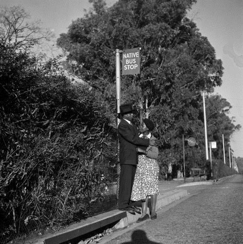 Bob Gosani's Love Story tells a layered story. On one level the image captures a moment between two lovers, standing at a bus stop, on a tree-lined street.  However, placed in a historical context, the photograph tells a deeper story. The shot was taken in Sophiatown in 1956, the year that the mixed-race suburb in Johannesburg was demolished and made a 'white' area according to the apartheid Group Areas Act.