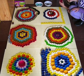 recycled plastic lid mosaic art and craft Looks like a good reason to collect bottle caps. I bet these look great in real life. I would use cheap tiles or foam core as a ground and glue the caps top down so they would stay glued. Looks like that is what they did here. Taking cap liners out is a nice fiddly task for the restless child.