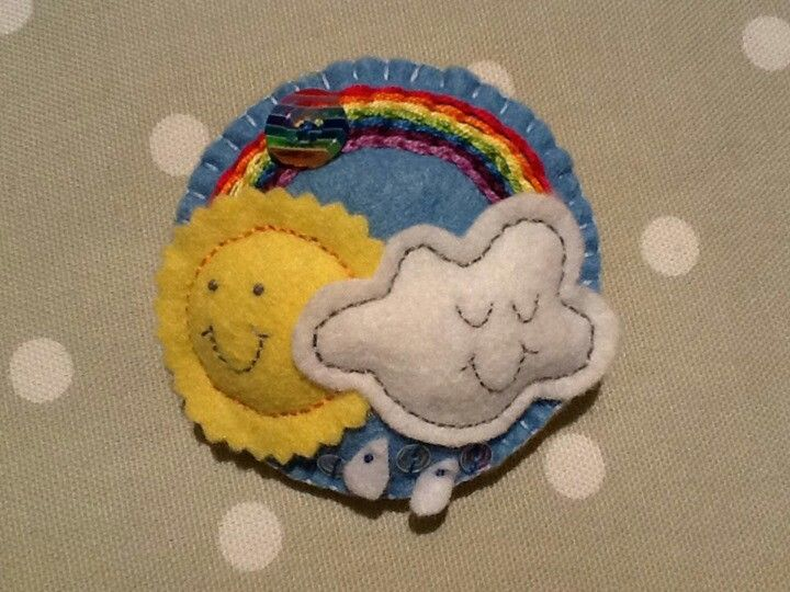 Handmade felt rainbow brooch in blue, with embroidery, sequins and button embellishments.