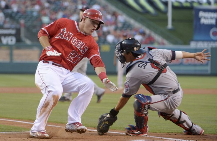 Jun 24, 2014; Anaheim, CA, USA; Los Angeles Angels center fielder Mike Trout (27) eludes the tag of Minnesota Twins catcher Kurt Suzuki (8) to score in the first inning at Angel Stadium of Anaheim. Mandatory Credit: Kirby Lee-USA TODAY Sports