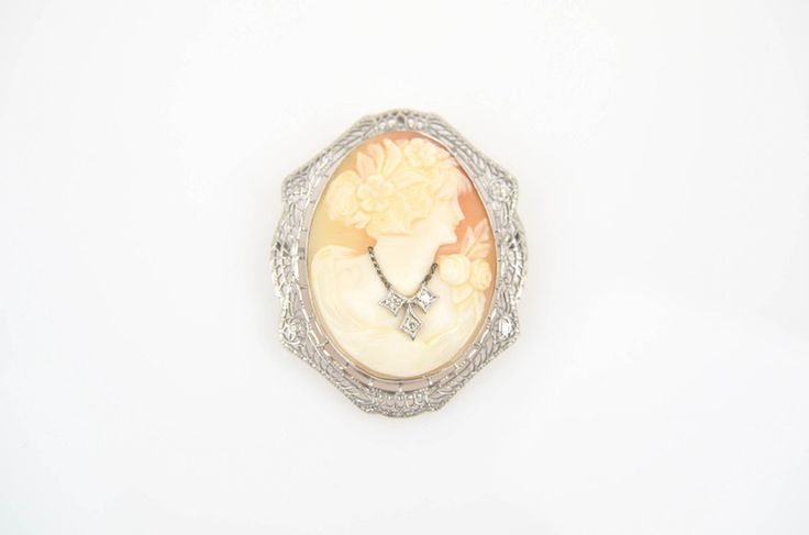 A 14K white gold cameo brooch with a filigree frame depicting a woman with flowers in her hair wearing a necklace of 0.12 ctw diamonds. Metal Type: 14K Gold Hallmarks: 14K Total Weight: 9.8 dwt Brooch or Pin Closure Type: Safety catch CENTER STONE Count and Type: 1 Shell Shape: Cameo
