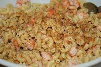 A macaroni salad with shrimp, onion, mayonnaise, seasoned with Old Bay, Cajun seasoning, lemon pepper and garlic salt. Chopped fresh tomatoes are tossed in just before serving.