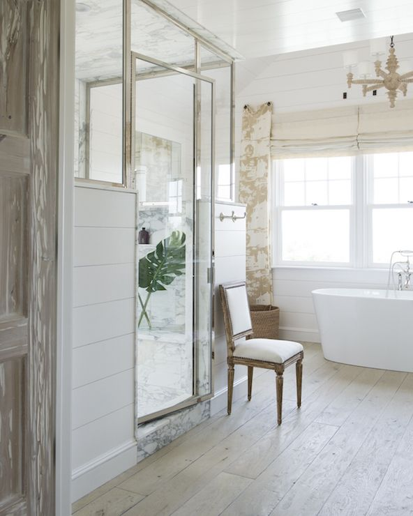 Amazing bathroom features a walk-in shower frame fitted with glass and chrome on top and shiplap on bottom fitted with a gray and white marble surround. A jute rope chandelier is suspended over an oval freestanding tub paired with a vintage style tub filler