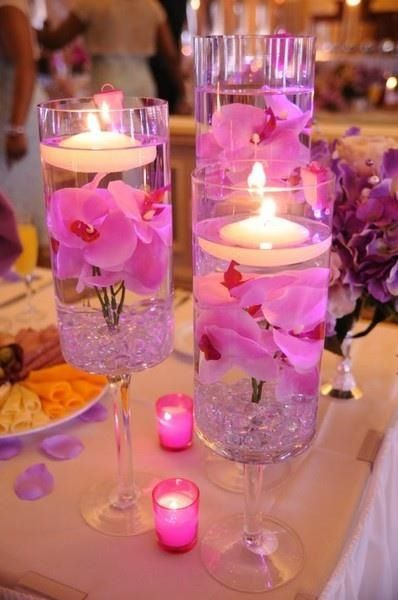 Simple centerpiece. Water, floating candle, gems from dollar tree and fake flowers. Glue the flowers to the bottom of vase first, add stones, water and candle and viola!