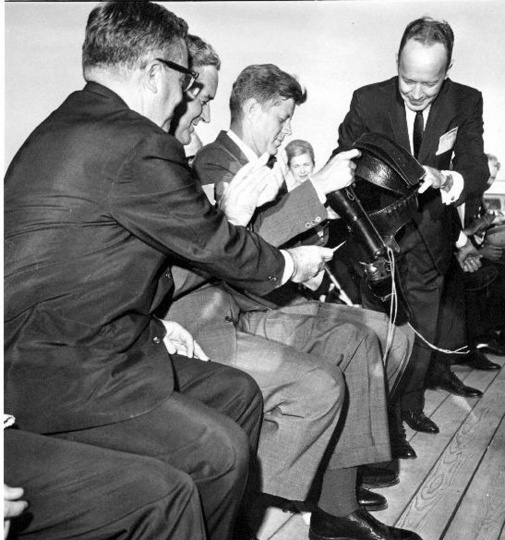 06 June 1963. SIX-SHOOTERS FOR JFK - President John F. Kennedy examines a pair of Western six-shooters presented to him, along with a Stetson hat, boots and Texas Ranger's badge, as the President arrived in El Paso Wednesday. Sen. Ralph Yarborough. D.-Tex., left, and Texas Gov. John Connally, second from left, watch as El Paso Mayor Judson Williams, right, makes the presentation.