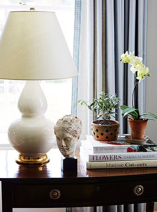A ceramic bust status, gold-accented table lamp and potted orchid will add a sense of timeless style in any home!
