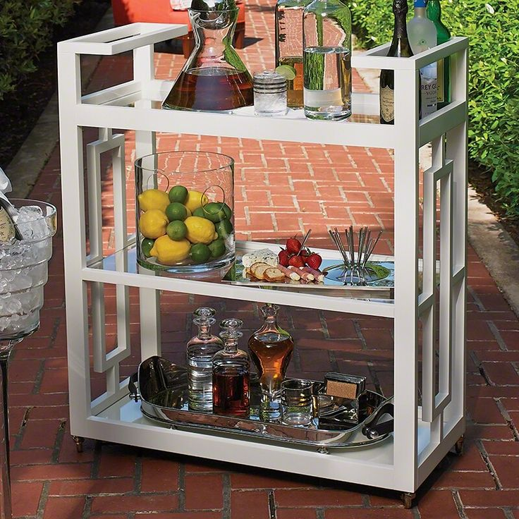 "Reminiscent of the entertainment of the mid-century, the Grid Block Bar Cart captures the geometric architecture and furniture of the time period. The matte white lacquer finish brings a sophisticated elegance to this modern design. Features integrated handles, three tiers of removable glass shelves, and fully rotational cast brass wheels.  Dimensions: Bottom to Mid Height: 15.25"" Mid to Top Height: 15"" Top Shelf to Handle Height: 6"""