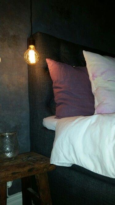 Skönaste sängen från carpe diem. Mörkt grå väggar i sovrummet. En rustik pall fungerar som nattduksbord.