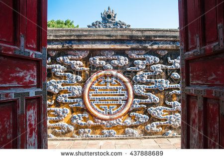 Hue Citadel Complex. The old gate and a wall decorated with traditional Vietnamese mosaic made of porcelain. Vietnam - stock photo