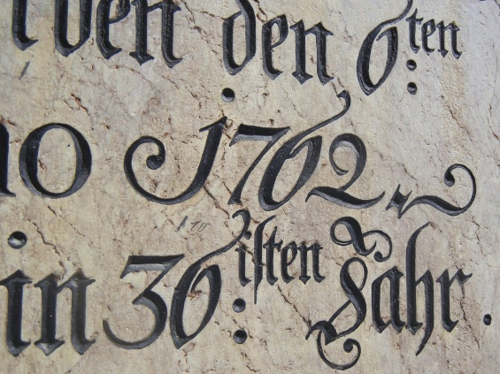 Roman numerals and broken script combined formally by the occasional ornamental verves only.  Seen on old stone tablets at St. Peter tower in Munich.