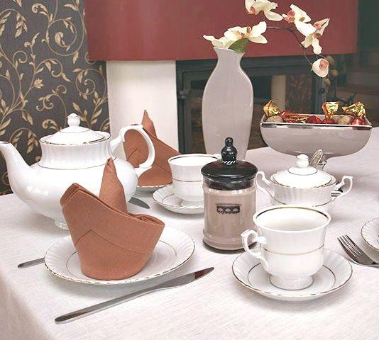 Obrus lniany biały oraz eleganckie serwetki lniane w kolorze rudym. Świeca zapachowa o wyjątkowym wyrafinowanym zapachu.
