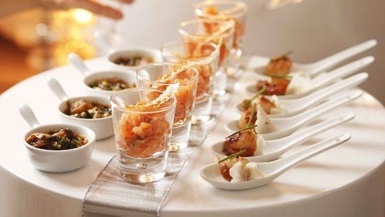 Aperitiefhapjes uit de zee : glaasje met zalm en een sesamkrokantje - lepeltje met sint-jacobsnoten en flinterdunne bloemkooltjes - mosseltje maître d'hôtel