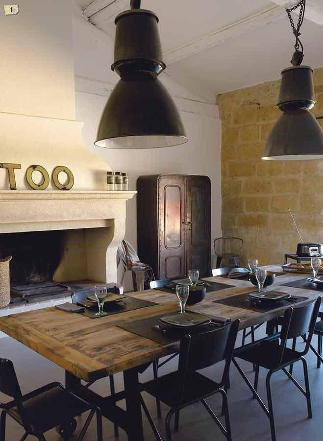 Suspension d'usine dans une salle à manger avec une grande table en bois entourée de chaises en métal noir et placées une cheminée de style en pierre