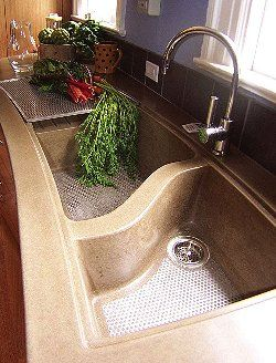 Pre-cast concrete sink with embedded stainless steel grate and stainless rinse tray.