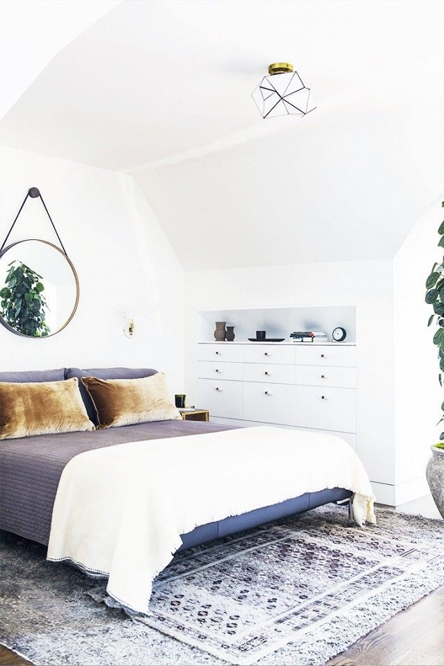 Modern bedroom with a morrocean rug, gray bedding, and a mirror